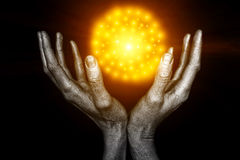 Silvery male hands with a yellow energy ball. On a black background stock image
