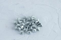 Silvery metal screws for plasterboard walls. On a gray concrete background. royalty free stock photography
