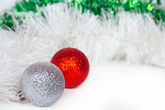 Silvery and red balls with Christmas tinsel Royalty Free Stock Photos