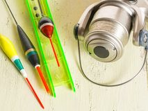 Spinning reel and floats with a wood. Fishing gear. Selective focus royalty free stock photo