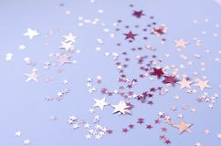 Silvery stars of different sizes on a blue background stock photos
