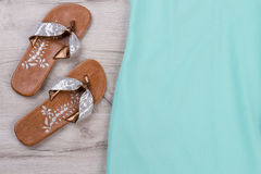 Silvery summer flip flops. Silvery summer flip flops and a detail of a turquoise dress stock image