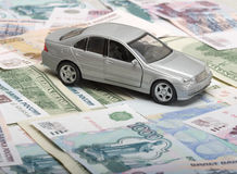 The silvery toy car. Against from monetary denominations Royalty Free Stock Photography