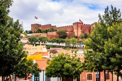 Silves, Faro, Algarve, Portugal. The walls of the imposing castle protrude above the city against the blue sky Royalty Free Stock Photo