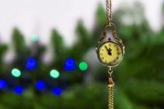 Silvesterabend, die Uhr - das Medaillon zeigt 23 55 Bald eine neue Zeit auf dem Hintergrund eines grünen Weihnachtsbaums stockfoto