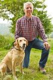 Silvicultor con el perro en naturaleza Imagenes de archivo