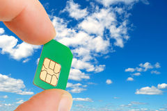 Sim card. Sim card in a man's hand against the background of sky Royalty Free Stock Images