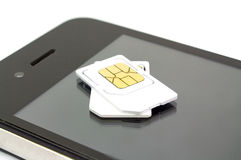 Sim card and smart phone on white background Royalty Free Stock Photos