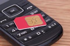 SIM Card sobre el teléfono Foto de archivo libre de regalías