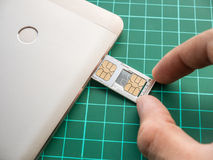 SIM Card Tray Filled with Nano SIM Card and Micro SIM Card Pushed with Hand. In Smartphone stock image
