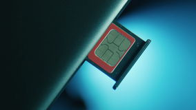 SIM cards in the slot in the cell phone. SIM card in the slot in the cell phone placed on a blue background stock video footage