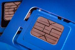 Sim karta używać mobilny mądrze telefonu zakończenie w górę makro- strzału na błękicie Obrazy Royalty Free