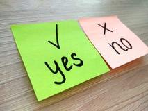 Sim ou nenhuma mensagem da pergunta em notas pegajosas com foco sobre sim no fundo de madeira da tabela imagem de stock royalty free