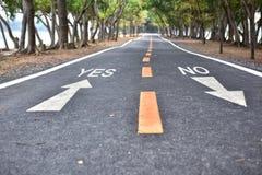 Sim ou nenhumas palavras com seta branca assine a marcação na estrada Imagem de Stock