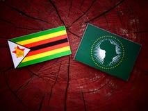 Simbabwe-Flagge mit Flagge der Afrikanischen Union auf einem Baumstumpf Stockbild