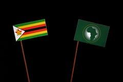 Simbabwe-Flagge mit Flagge der Afrikanischen Union auf Schwarzem Lizenzfreie Stockfotos