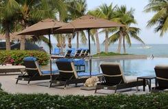 Simbassäng för lyxigt hotell med dagdrivare och solparaplyer Arkivfoton