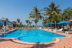 Simbassäng med blått vatten i tropisk semesterort med palmträd Arkivbild