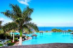 Simbassäng och strand på det lyxiga hotellet royaltyfria foton