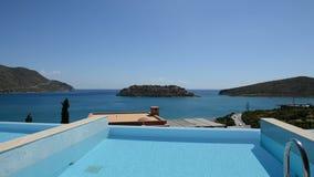 Simbassäng på den lyxiga villan med sikt på den Spinalonga ön arkivfilmer