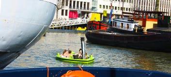 Simbassäng som svävar i vattnet av floden eller kanalen av porten av Rotterdam Unga holländska studenter har gyckel och spende royaltyfria foton