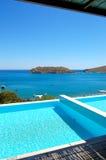 Simbassäng vid den lyxiga villan med en beskåda på den Spinalonga ön Arkivfoto