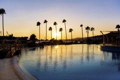 Simbassängen för det lyxiga hotellet med gömma i handflatan på solnedgången Arkivbild