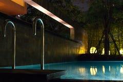 Simbassängområde på natten med mjuk glödande utomhus- belysning i dyrt hem i tropiska South East Asia med plant vatten och ro royaltyfri bild