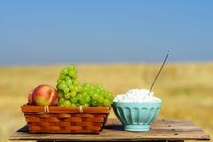 Simboli della festa ebrea - Shavuot Primo habikkurim di frutti in formaggio ebraico e bianco sulla tavola di legno immagini stock