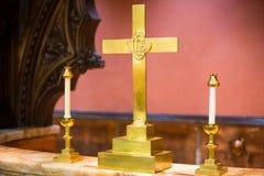 Simboli di religione all'incrocio ed alle candele dell'altare della chiesa Fotografia Stock
