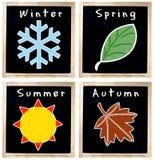Simboli di stagioni sulla lavagna Fotografia Stock Libera da Diritti