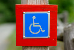 Simbolo blu disattivato segno di handicap della sedia a rotelle Immagini Stock Libere da Diritti