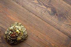 Simbolo buddista (JPG +EPS) Rospo fornito di gambe di Orientale tre con le monete di oro sullo spazio di legno scuro della copia  fotografia stock