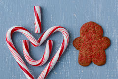 Simbolo del cuore di Candycane su legno blu con l'uomo di pan di zenzero Fotografie Stock