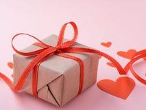 Simbolo del giorno del ` s del biglietto di S. Valentino - contenitore di regalo in carta marrone di Kraft con la a Immagine Stock