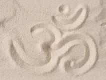 Simbolo del OM in sabbia fotografie stock