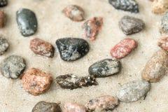 Simbolo dell'elica del ciottolo sul fuoco selettivo della sabbia Immagini Stock Libere da Diritti