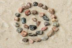 Simbolo dell'elica del ciottolo sul fuoco selettivo della sabbia Fotografia Stock