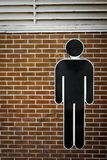 Simbolo dell'uomo sul muro di mattoni Immagine Stock Libera da Diritti