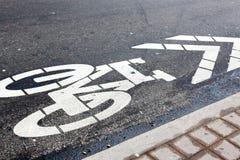 Simbolo della bicicletta sulla strada in una via Fotografie Stock Libere da Diritti