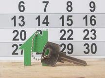 Simbolo della casa con la chiave d'argento su fondo di legno d'annata Immagini Stock