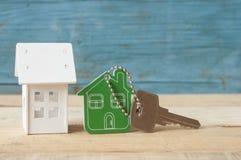 Simbolo della casa con la chiave d'argento su fondo di legno d'annata Immagini Stock Libere da Diritti
