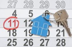 Simbolo della casa con la chiave d'argento su fondo di legno d'annata Immagine Stock