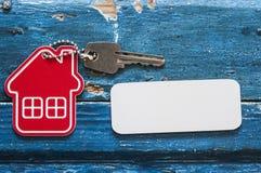 Simbolo della casa con la chiave d'argento su fondo di legno d'annata Immagine Stock Libera da Diritti