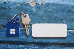 Simbolo della casa con la chiave d'argento su fondo di legno d'annata Fotografia Stock