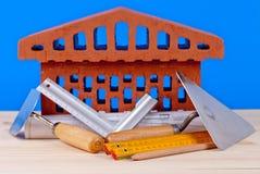 Simbolo della casa del mattone e strumenti del muratore Immagini Stock