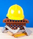 Simbolo della casa del mattone e strumenti del muratore Fotografie Stock Libere da Diritti