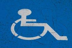 Simbolo della sedia a rotelle sul punto di parcheggio di handicap immagine stock