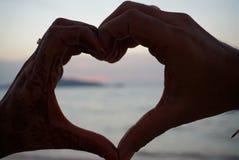 Simbolo delle mani delle coppie di amore che fanno forma del cuore fotografia stock