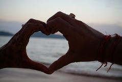 Simbolo delle mani delle coppie di amore che fanno forma del cuore immagine stock libera da diritti